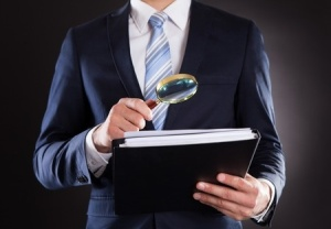 Businessman reviewing documents with magnifying glass