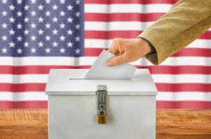 47062864 - man putting a ballot into a voting box - usa